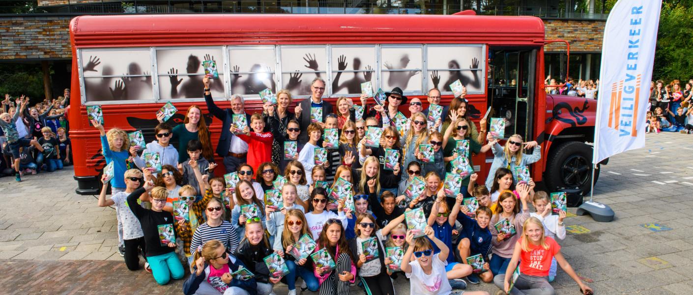 De Griezelbus van Paul van Loon met de schoolkinderen en directeuren op het schoolplein