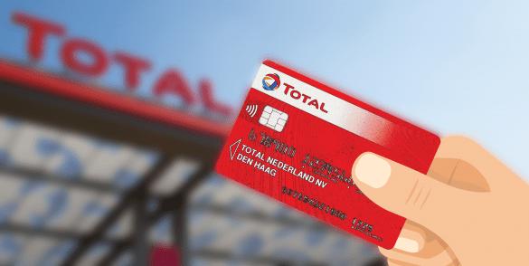 Rode total kaart met een hand en op de achtergrond een total tankstation.
